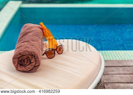 Suntan vacation hotel swimming pool background with travel accessories to tan on sun loungers holidays in Caribbean destination. Tanning oil, towel and sunglasses women objects.