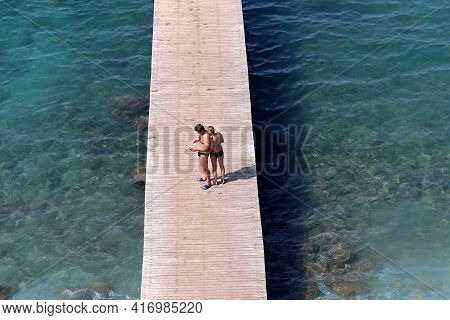 Kusadasi, Turkey - September 2020: Couple Standing On A Wooden Pier On Sea Background, Aerial View
