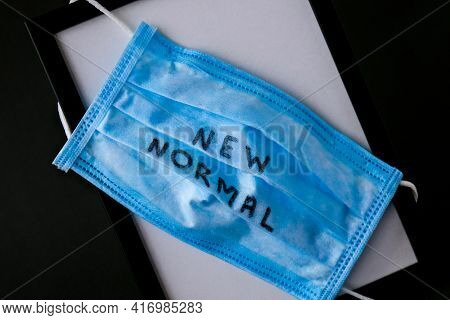 New Normal Text Written On Blue Surgical Or Medical Mask. Used Dirty Face Mask. Problem Of Unhygieni