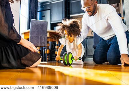 African Family Working Out At Home With Children Exercises With Ab Wheel Abs