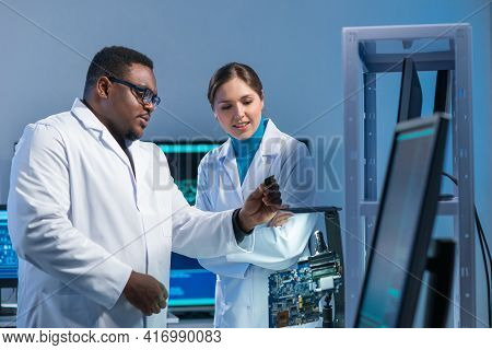 Diverse Team Of Microelectronic Engineers Discuss Current Developments In A Science Lab. Workplace O