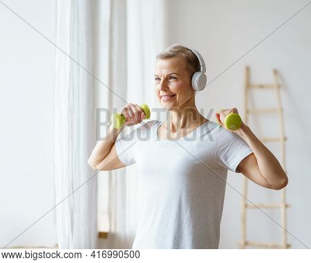 Portrait Of Smiling Senior Woman Exercising Fitness With Dumbbells At Home. Mature Female Build Up B
