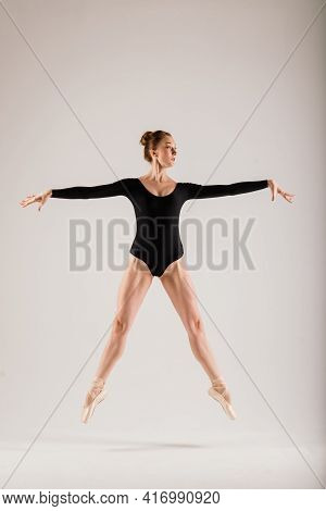 Portarit Of Sensual Professional Caucasian Callet Dancer In Body Suit And Pointes Shoes On White.