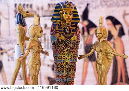 Still Life With Egyptian Figures Of Anubis, Pharaoh And The Goddess Nebtht And Eset. In The Backgrou