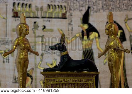 Still Life With Egyptian Figures Of Anubis And The Goddess Nebtht And Eset In Gold. In The Backgroun