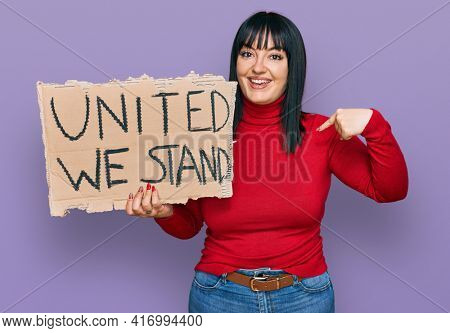 Young hispanic woman holding united we stand banner pointing finger to one self smiling happy and proud