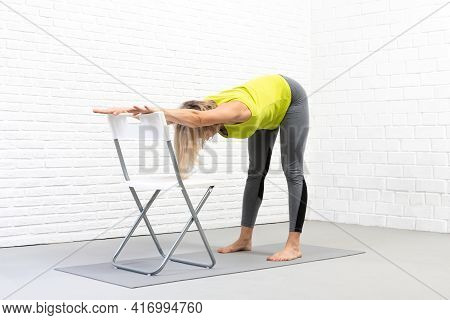 Back And Hamstrings Stretching, Yoga Indoor With A Props. Caucasian Woman Does Deep Bend Holding On