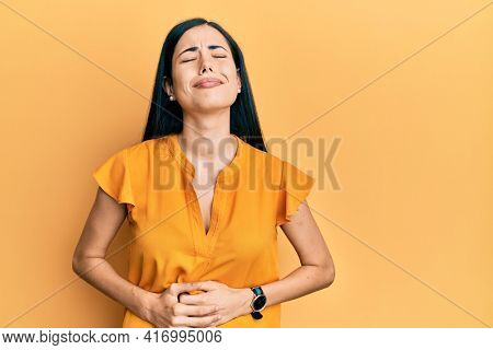 Beautiful young woman wearing casual clothes with hand on stomach because nausea, painful disease feeling unwell. ache concept.