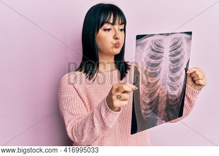 Young hispanic woman holding chest x-ray puffing cheeks with funny face. mouth inflated with air, catching air.
