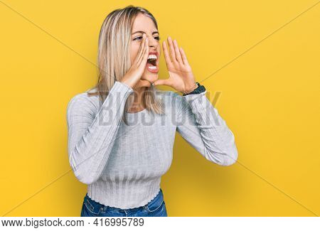 Beautiful blonde woman wearing casual clothes shouting angry out loud with hands over mouth