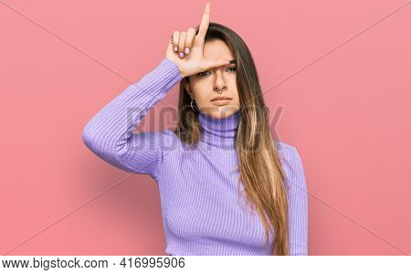 Young hispanic woman wearing casual clothes making fun of people with fingers on forehead doing loser gesture mocking and insulting.