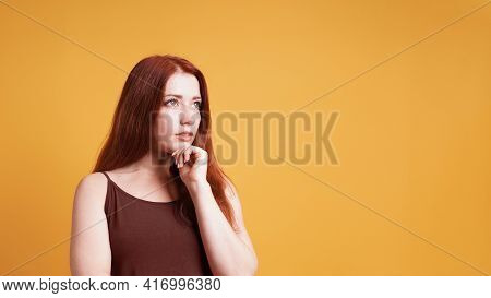 Contemplating Young Woman Thinking With Hand On Chin Gesture Looking Up To Copy Space