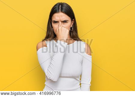Young hispanic woman wearing casual clothes smelling something stinky and disgusting, intolerable smell, holding breath with fingers on nose. bad smell