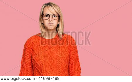 Beautiful blonde woman wearing casual clothes and glasses puffing cheeks with funny face. mouth inflated with air, crazy expression.
