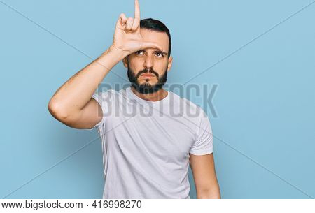 Young man with beard wearing casual white t shirt making fun of people with fingers on forehead doing loser gesture mocking and insulting.