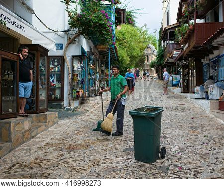 Kas, Turkey - 16 October, 2019: Street cleaning in old town, Trash can stands on stone paved road, Janitor with broom and shovel is talking to shopkeeper on tourist street