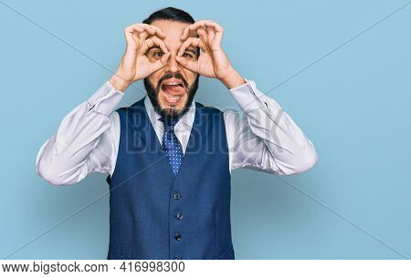 Young man with beard wearing business vest doing ok gesture like binoculars sticking tongue out, eyes looking through fingers. crazy expression.