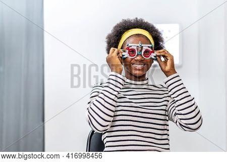 Smiling Young Woman African American Checking Vision With Eye Test Glasses During A Medical Examinat