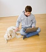 teenager with a laptop computer and his dog on a parquet floor poster