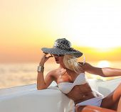 Young sexy woman in white bikini enjoying the sunset on her private yacht poster