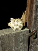 A piggy bank sitting on the barn door at the farm. poster