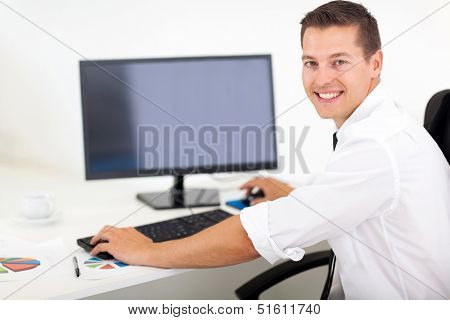 good looking businessman working on a computer in office