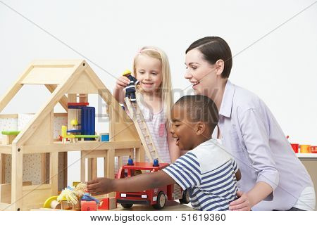 Pre-School Teacher And Pupils Playing With Wooden House