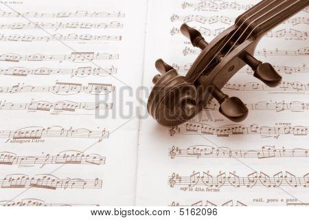 Vintage Violin Neck Resting On A Sheet Music