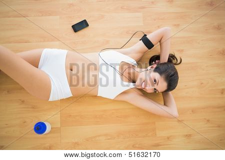 Fit happy woman doing sit ups listening to music at home on parquet floor