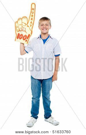 Young Boy Wearing A Large Foam Hand
