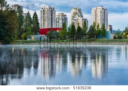 Condo Buildings Reflected In Lake With Trees