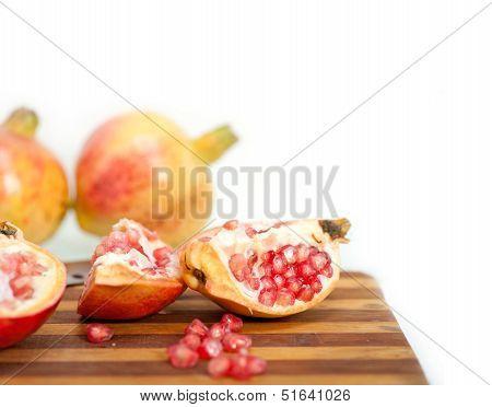 fresh pomegranate fruit on wood over white background poster