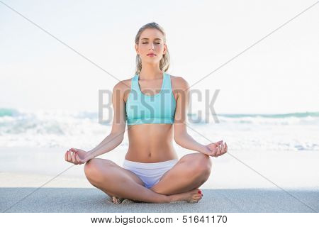 Relaxed slender blonde in sportswear meditating on a sunny beach