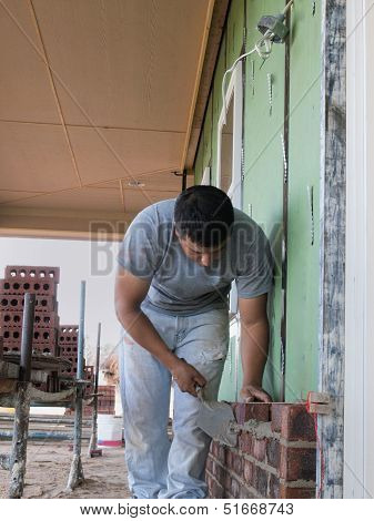 Bricklayer Removing Mortar