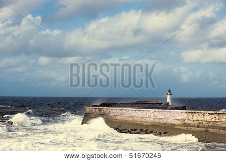 Waves crashing against the sea wall with lighthouse at Whitehaven, England, UK poster