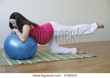 Young Pregnant Woman Doing Leg Muscle Exercise With Fitness Ball.