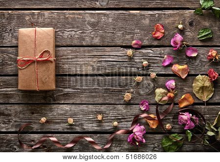 Craft gift box with rose petals and dried flowers on old wooden plates. Lovely holiday background.