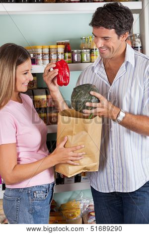 Happy mid adult woman with man putting bellpepper and pumpkin in paper bag at supermarket