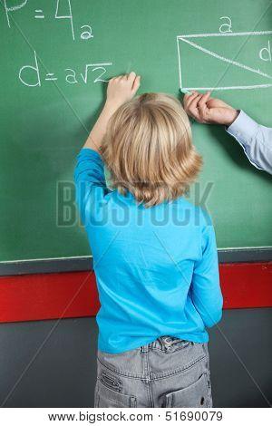Rear view of little boy writing formula on greenboard in classroom