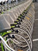 A long row of green rental bicycles with baskets poster
