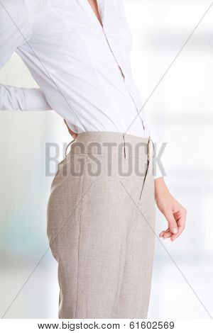 Woman with back pain holding her aching hip  poster