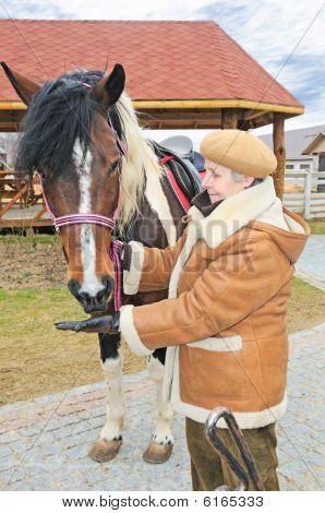 Elderly Woman Feed Horse