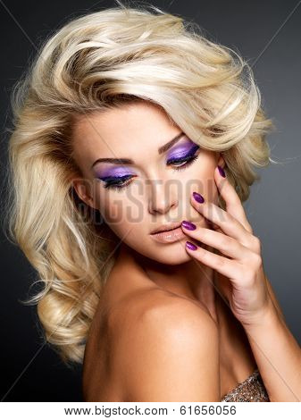 Beautiful blond woman with beauty purple manicure and makeup of eyes. Fashion model with curly hairstyle.
