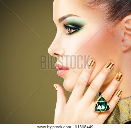 Glamour woman with beautiful golden nails and emerald ring on hands