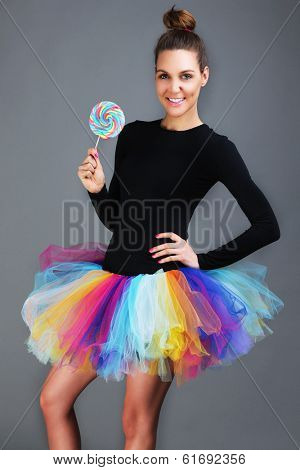A picture of a happy fashionable woman posing with a lollipop over gray background