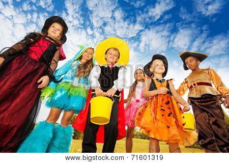 Group of kids in Halloween costumes looks down