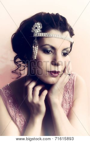Closeup in vintage colors of a 1920s style young woman with diamond headdress and flapper dress