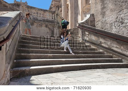 DUBROVNIK, CROATIA - MAY 28, 2014: Japanese tourists sitting on Jesuits staircase, the grand staircase that leads from Gundulic Square to square in front of Collegium Ragusinum and St. Ignatius Church