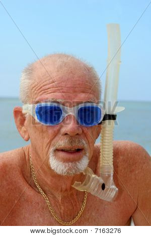 Older man in blue goggles and snorkel gear