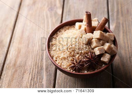 Brown sugar cubes and crystal sugar with spices in bowl on wooden background